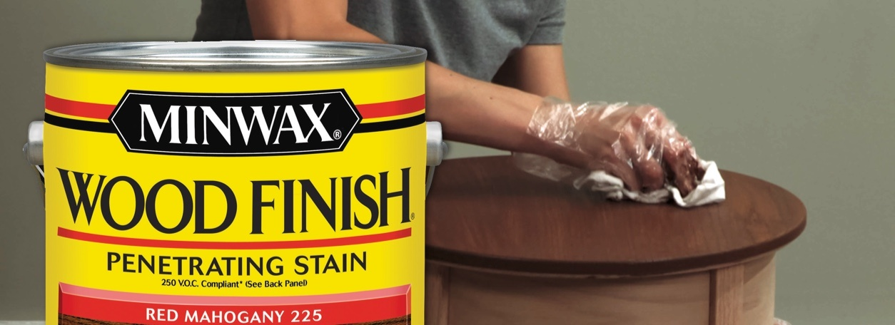 Minwax wood stain can with person staining table in background